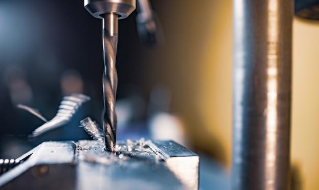 Процесс сверления с крупным планом стружки, сверлильный станок на рабочем месте слесаря-слесаря-слесаря