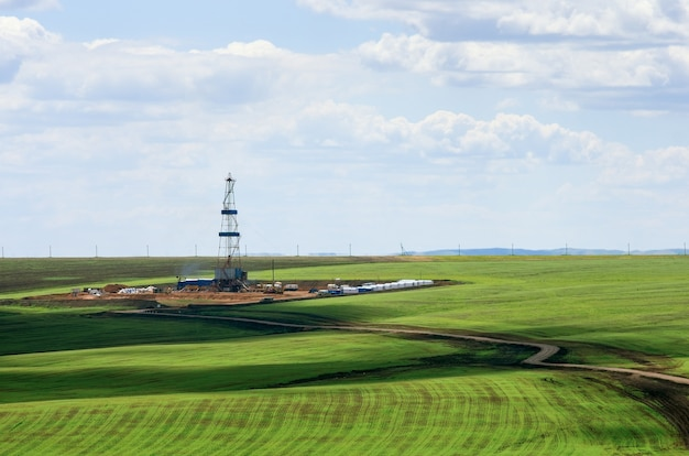 Drilling rig among agricultural fields. view from above