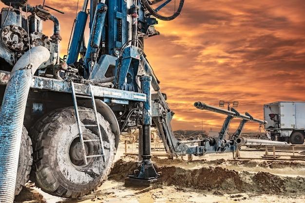 드릴링 장비는 일몰 시 현장에서 작동합니다. 확대. 깊은 구멍 드릴링. 지질 탐사 작업. 광물 탐사. 강력한 드릴 드릴.