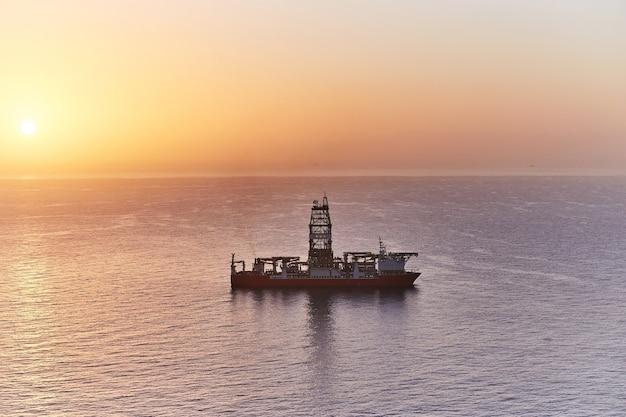 드릴링 선박 드릴링 유정 바닥 바다 선반. 해질녘 바다의 지질 탐사 가스 및 유전