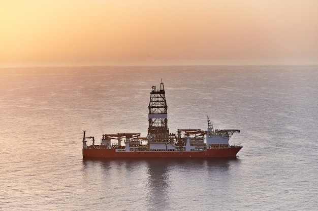 Drilling ship drilling oil well bottom ocean shelf. geological exploration gas and oil fields in sea at sunset