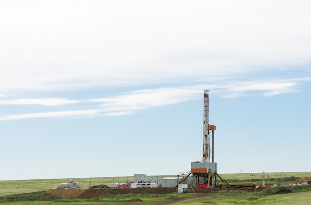 Drilling tower in the steppe steppe landscape with drilling rigs and equipment