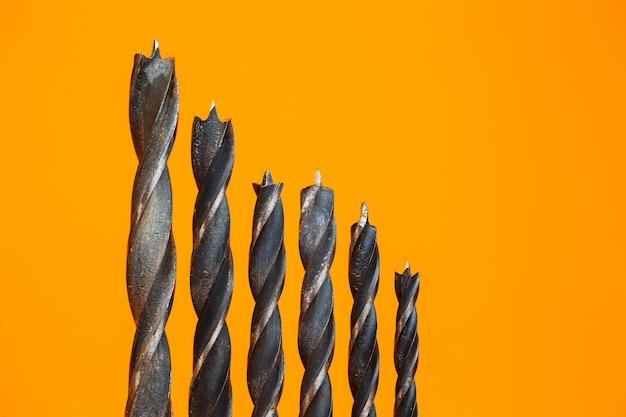 オレンジ色の背景のドリル用のさまざまなサイズの木材用ドリル。建設ツール