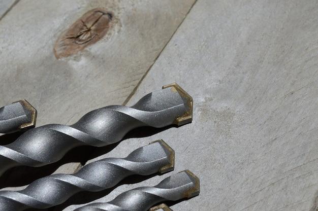 임팩트 드릴용 카바이드 팁이 있는 드릴은 판자 나무 배경에 놓여 있습니다. 확대.