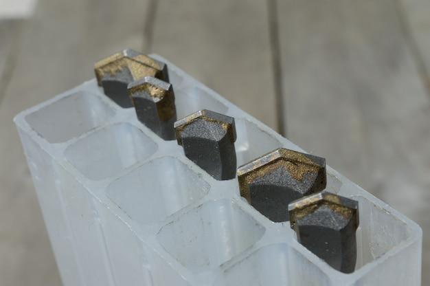 카바이드 팁 해머 드릴 비트가 있는 드릴은 판자 나무 배경의 플라스틱 케이스에 있습니다. 확대.