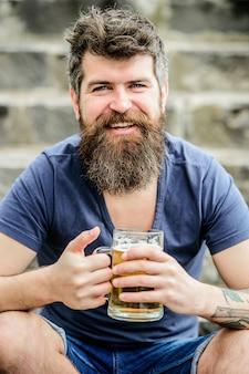 アルコールビール飲料を飲みます。週末はリラックスしてください。残忍な男性はリフレッシュが必要です。ビールを飲むひげの髪を持つ成熟したヒップスター。屋外のビアグラスを持つひげを生やした男。最高のビールを醸造します。
