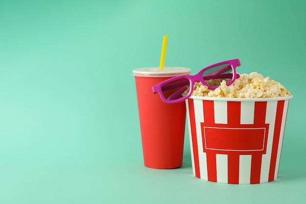 Drink, bucket with popcorn and 3d glasses on mint space