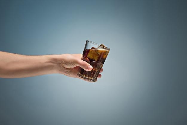 手でグラスにコーラを飲む