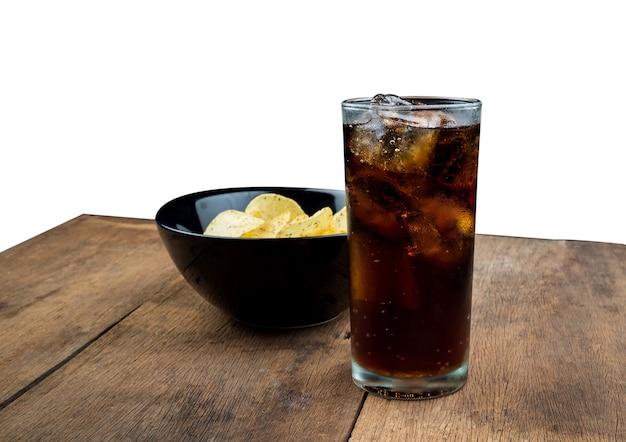 白い背景の上の古い木製のテーブルでガラスの氷とコーラを飲む