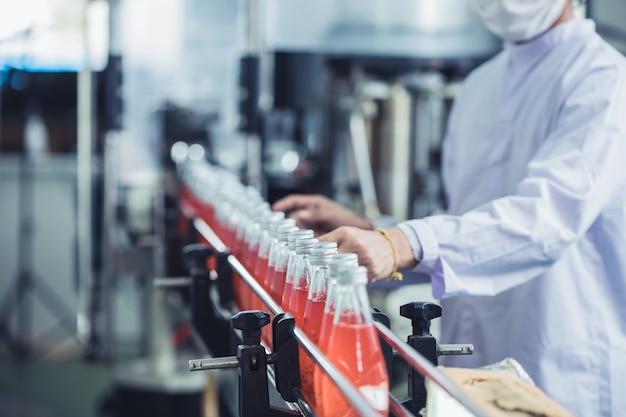 Фабрика напитков - работник гигиены крупным планом работает проверяет стакан сока в бутылках на производственной линии