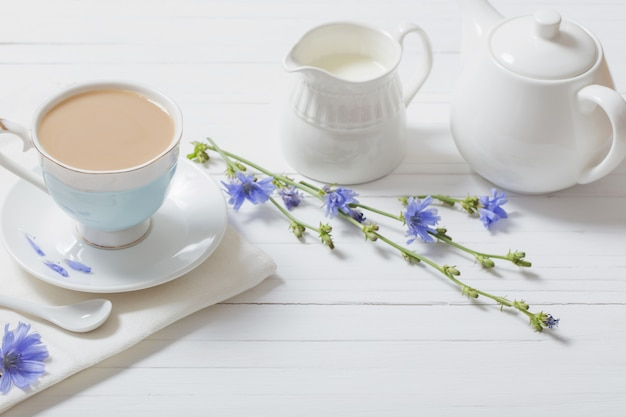 Drink from chicory in a cup on the white wooden table