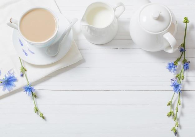 白い木製のテーブルの上にカップのチコリから飲む