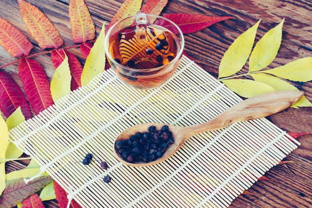 Drink from dried hawthorn berries in wooden spoon on the table with colorful autumn leaves.