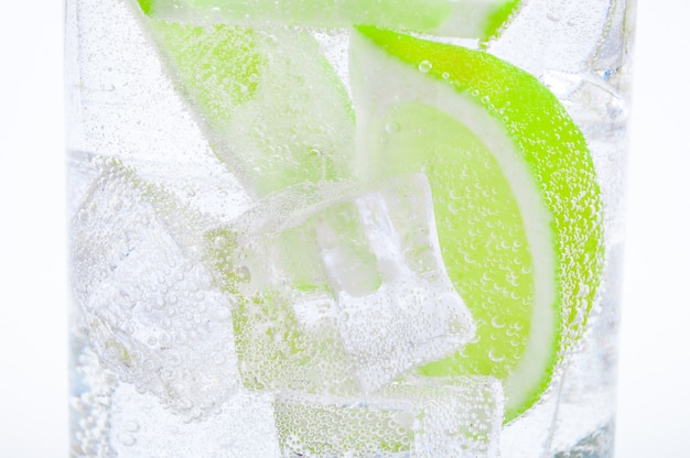 Drink from ice, lumps of fresh juicy green lime and crystal clear water in a glass.