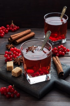 ガラスカップの赤いガマズミの果実から飲みます。