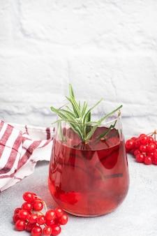 ガラスカップの赤いガマズミの果実から飲む