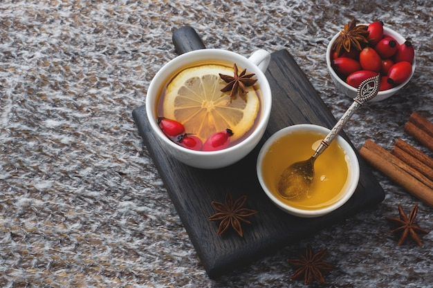 Drink from wild rose berries with lemon and honey cinnamon. vitamin useful decoction of rose hips. cozy home concept of winter drink copy space