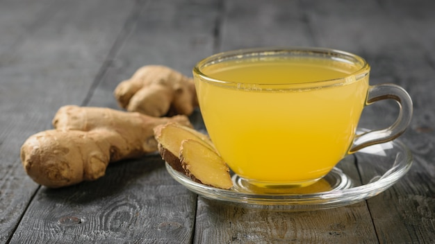 Drink and ginger and citrus and ginger root on a black wood table.