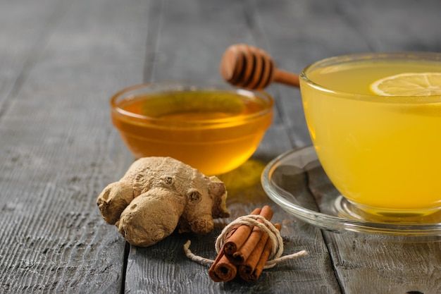 A drink of ginger, honey and citrus fruits to strengthen the immune system on the black wooden table.