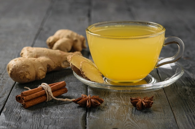 A drink of ginger root and citrus and a bunch of cinnamon sticks on a black wooden table.