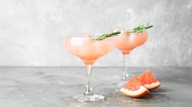 ライトグレーのコンクリートの2つのエレガントなガラスのゴブレットでグレープフルーツローズマリーと氷を飲む
