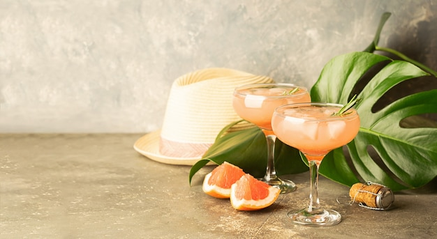 Drink grapefruit rosemary and ice in two elegant glass goblets on gray concrete