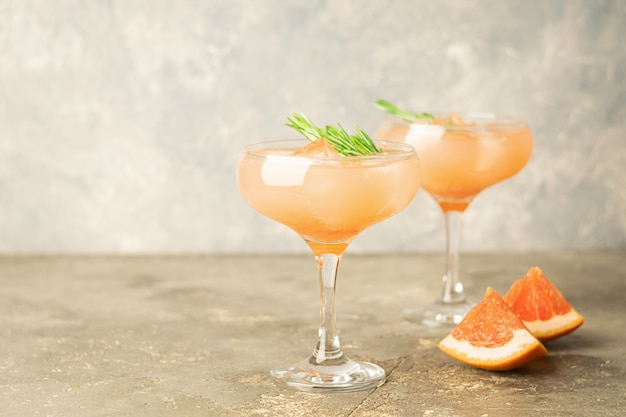 Drink grapefruit rosemary and ice in two elegant glass goblets on light gray concrete