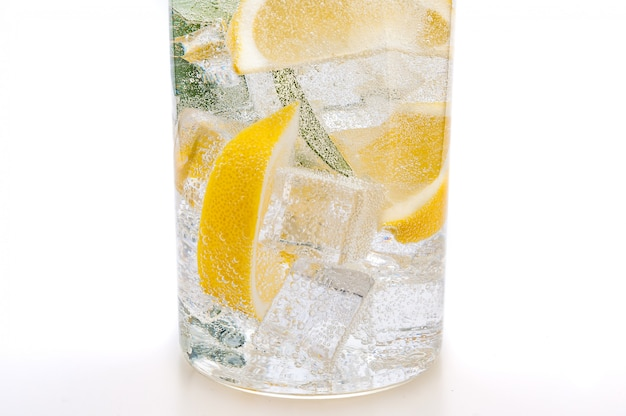 Drink of ice, the lobules of fresh juicy yellow lemon and crystal water in a glass.
