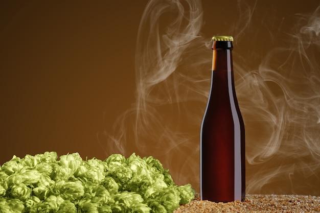 モックアップシリーズを飲みます。煙のあるアンバースタジオの背景に小麦とホップの円錐形の上に立つ茶色のビール瓶。デザインですぐに使用できるテンプレート。