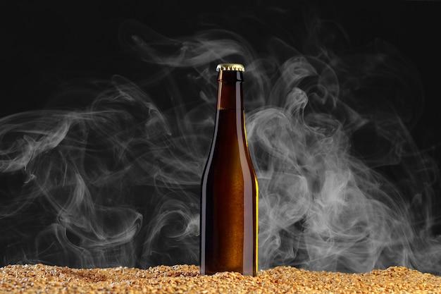 モックアップシリーズを飲みます。明るい煙で暗いスタジオの背景に小麦の粒の上に立つ反射の茶色のビール瓶。ショーケースですぐに使用できるテンプレート。