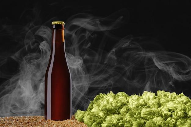 モックアップシリーズを飲みます。小麦とホップの円錐形の上に立っている反射のある茶色のビール瓶。ショーケースですぐに使用できるテンプレート。