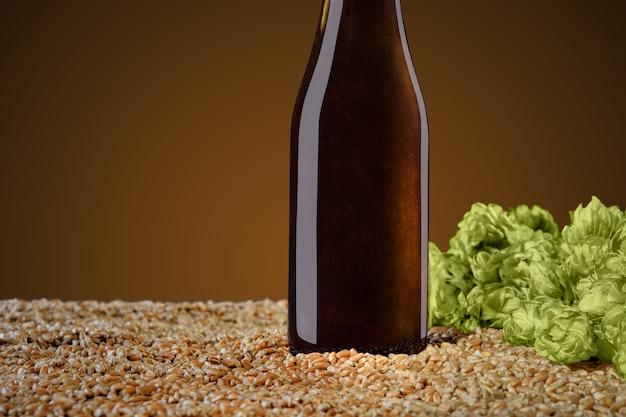 モックアップシリーズを飲みます。アンバースタジオの背景に小麦とホップの円錐形の上に立つ反射の茶色のビール瓶。テンプレートはデザインに使用できます。