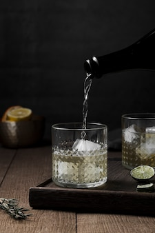 Drink pouring in glass with ice cubes