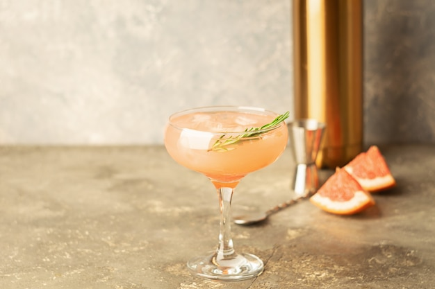 Drink rosemary grapefruit and ice in an elegant glass goblet on light gray concrete