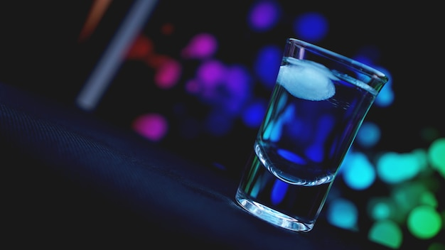 Drink shot with ice in bar on neon color abstract background