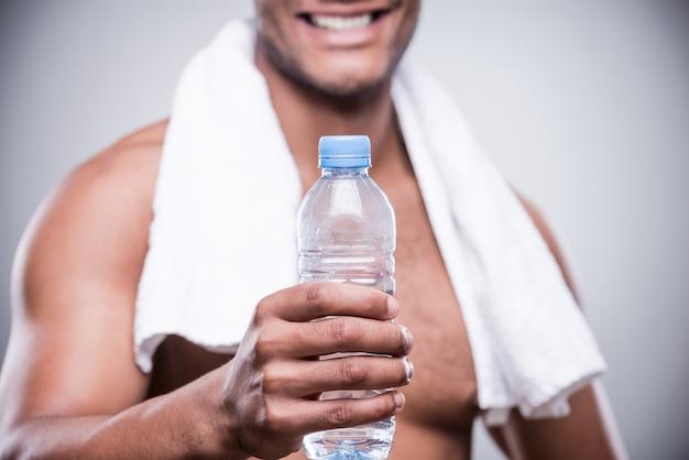 물 좀 마셔! 물 한 병을 기지개 하는 벗은 아프리카 남자의 자른 이미지