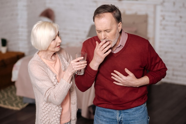 물 좀 마셔. 그의 사랑하는 아내가 그에게 물 잔을 제공하는 동안 노인 아픈 남자가 서서 강하게 기침합니다.