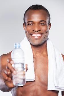 물 좀 마셔! 젊은 근육질의 아프리카 남자가 손에 물을 들고 병을 내밀고 웃고 있다
