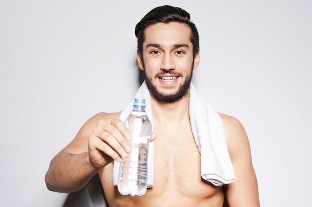 물 좀 마셔! 회색 배경에 서서 웃고 있는 젊은 근육질의 남자