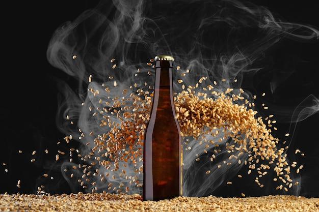 음료 템플릿 시리즈. 무겁게 산란 밀 곡물과 연기 검은 배경에 반사와 갈색 맥주 병. 디자인에 사용할 준비가 된 모형.