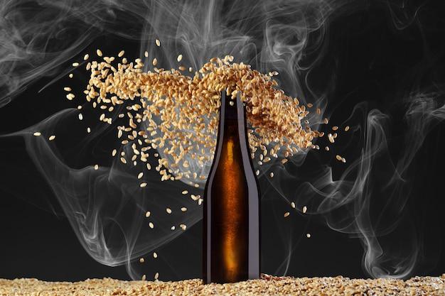 음료 템플릿 시리즈. 우아하게 산란 밀 곡물과 연기 어두운 배경에 반사와 갈색 맥주 병. 쇼케이스에서 사용할 준비가 된 모형.
