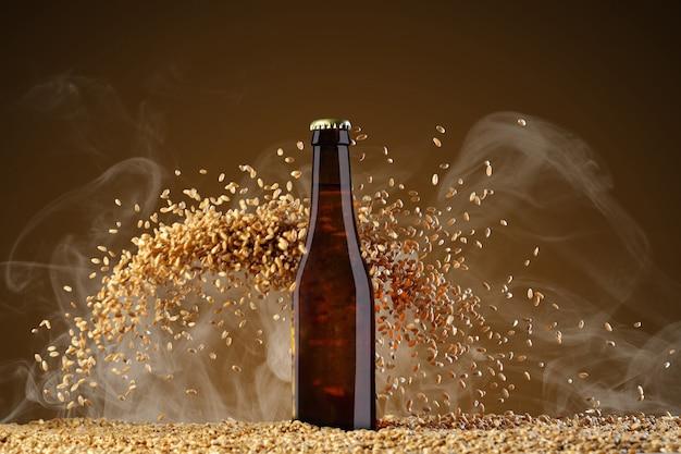 음료 템플릿 시리즈. 무겁게 산란 밀 곡물과 연기 umber 배경에 반사와 갈색 맥주 병. 쇼케이스에서 사용할 준비가 된 모형.
