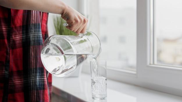 Пить воду. женская рука наливает свежую чистую воду из кувшина в стакан. здоровье и красота.