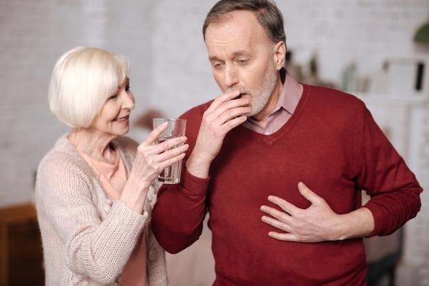 물 마시기. 아내가 물 한 잔을 제공하는 동안 서서 기침하는 기관지염이있는 노인.