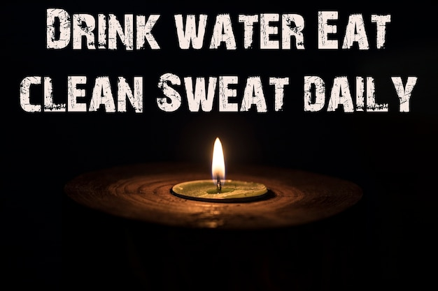 Drink water eat clean sweat daily - white candle with dark background - in a wooden candlestick.