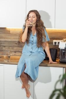 水を飲む。健康とダイエットのコンセプトです。健康的な生活様式。ヘルスケアと美容。水分補給。幸せな笑顔の肖像新鮮な水のガラスを持つ若い巻き毛の女性。健康的な食事。