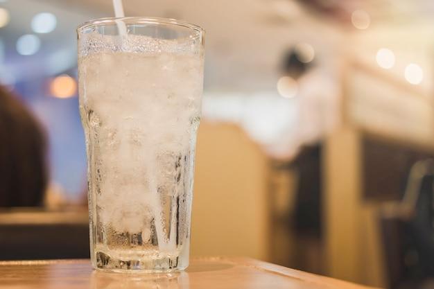 Пейте воду со льдом на столе в ресторане фон с винтажным фильтром