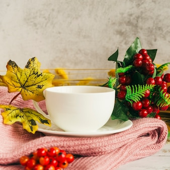 Drink with autumn leaves on scarf