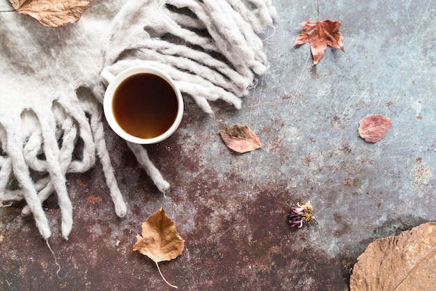 Drink with autumn scarf on shabby surface