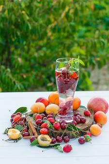 Bere con frutta, spezie, tagliere, foglie in un bicchiere su fondo in legno e giardino, vista laterale.